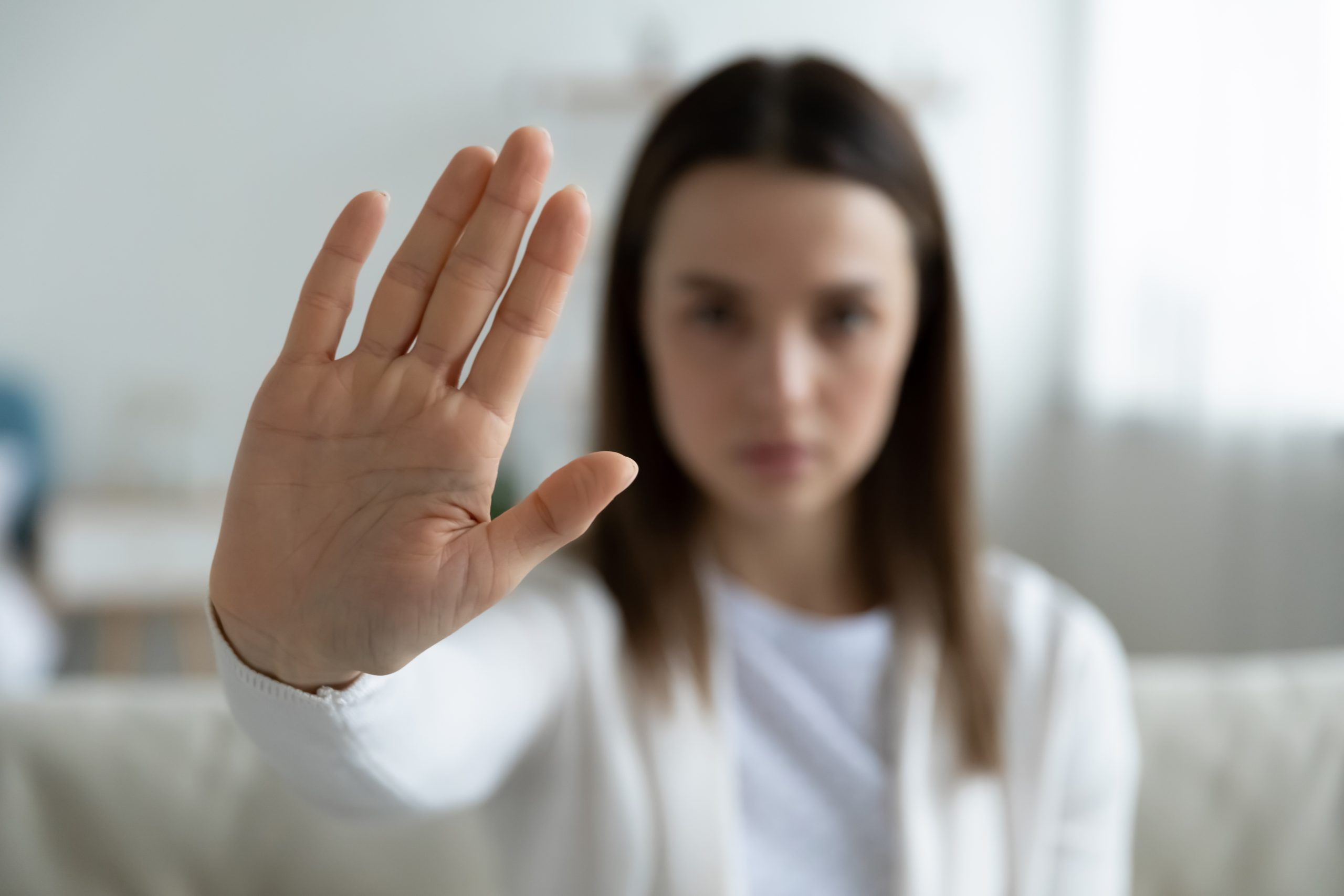 Close up focus on female hand showing stop gesture, protesting against domestic abuses or violence. Decisive woman saying no to abortion, denying gender discrimination, nonverbal language concept.